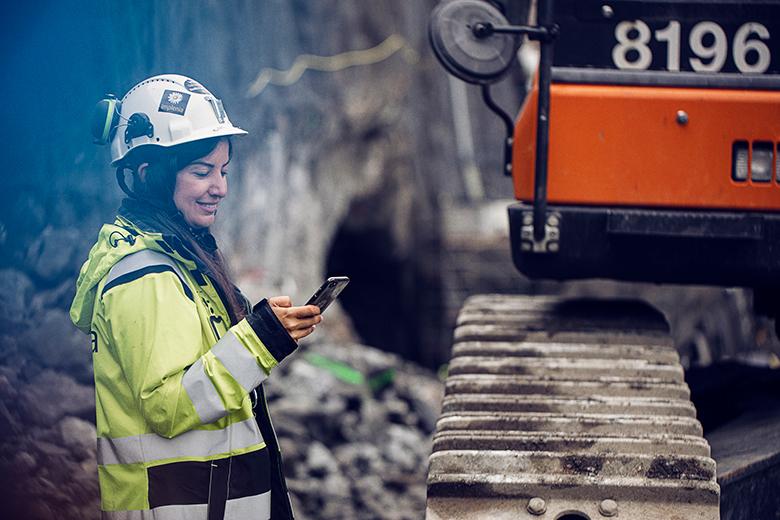 Tjej på byggarbetsplats som kollar på mobil